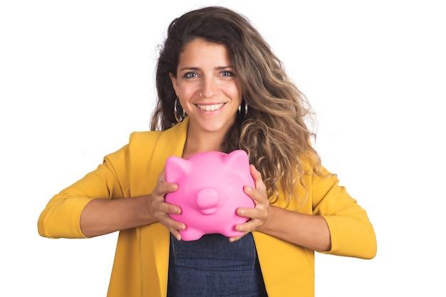 Retrato de uma jovem mulher bonita segurando um cofrinho parede branca isolada. salve o conceito de dinheiro.