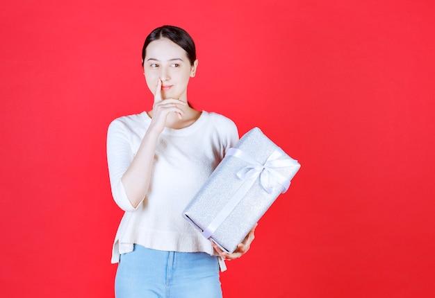 Retrato de uma jovem mulher bonita segurando uma caixa de presente e pensando