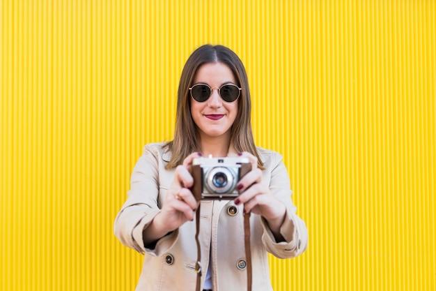 Retrato de uma jovem mulher bonita segurando uma câmera vintage sobre amarelo.