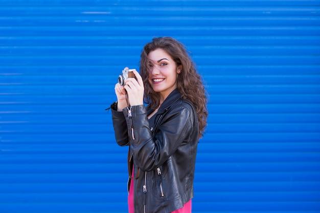 Retrato de uma jovem mulher bonita segurando uma câmera vintage sobre azul.