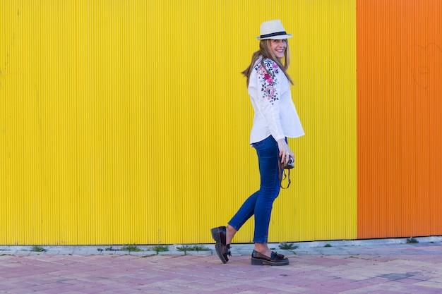 Retrato de uma jovem mulher bonita segurando uma câmera vintage sobre parede amarela
