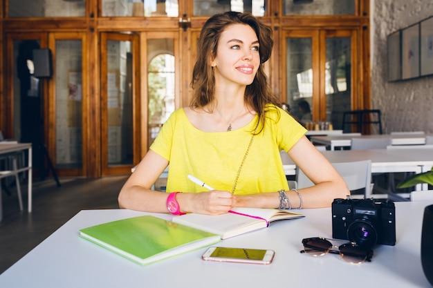 Retrato de uma jovem mulher bonita sentada à mesa, aprendizagem dos alunos, educação, sorrindo, escrevendo notas no livro diário