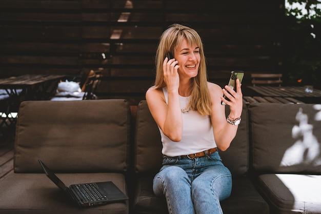 Retrato de uma jovem mulher bonita sentada com um laptop e um telefone no sofá em uma área de trabalho aconchegante