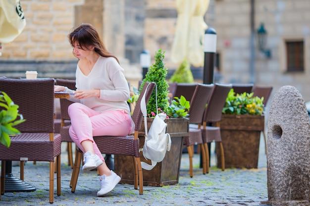 Retrato de uma jovem mulher bonita sentada num café ao ar livre, bebendo café. turista feliz com jornal no restaurante openair