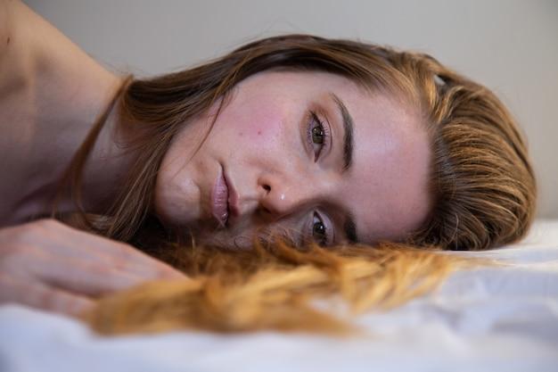 Retrato de uma jovem mulher bonita solitária com cabelos castanhos, deitada na cama e olhando