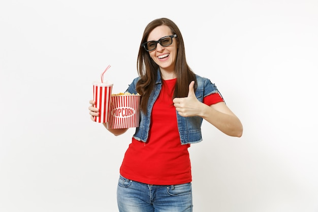 Retrato de uma jovem mulher bonita sorridente em óculos 3d, assistindo a um filme, segurando um balde de pipoca e um copo plástico de refrigerante ou coca-cola, aparecendo o polegar isolado no fundo branco. emoções no cinema.