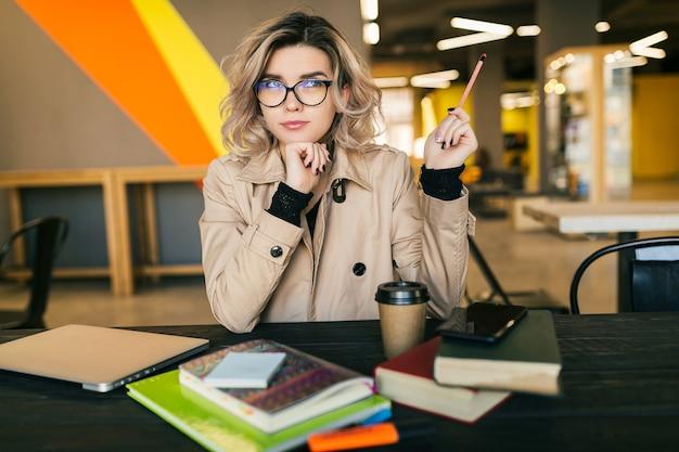 Retrato de uma jovem mulher bonita, tendo uma ideia, sentada à mesa com gabardine, trabalhando no laptop