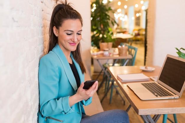 Retrato de uma jovem mulher bonita usando telefone celular em um restaurante. ela está sorrindo. vida moderna de um blogueiro com computador laptop, tablet, notebook e café na mesa. roupas casuais. estilo de vida