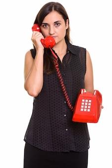 Retrato de uma jovem mulher bonita usando um telefone antigo