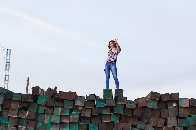 Retrato de uma jovem mulher bonita vestindo roupas casuais, de pé sobre uma montanha de blocos de madeira verdes