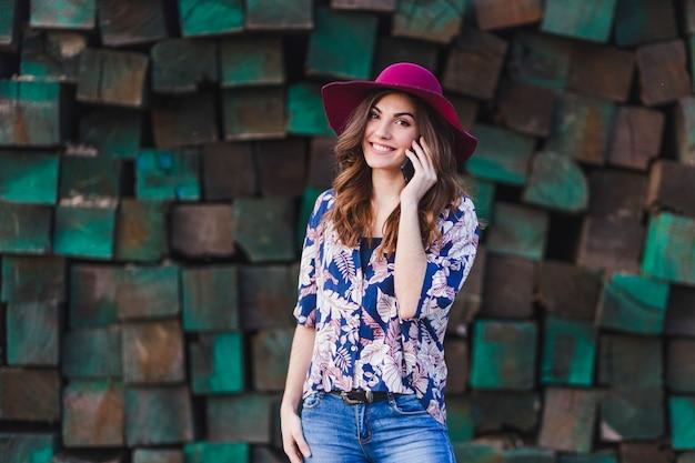 Retrato de uma jovem mulher bonita vestindo roupas casuais e um chapéu moderno e falando em seu telefone móvel. ela está de pé sobre o fundo verde de blocos de madeira e sorrindo. estilo de vida ao ar livre.