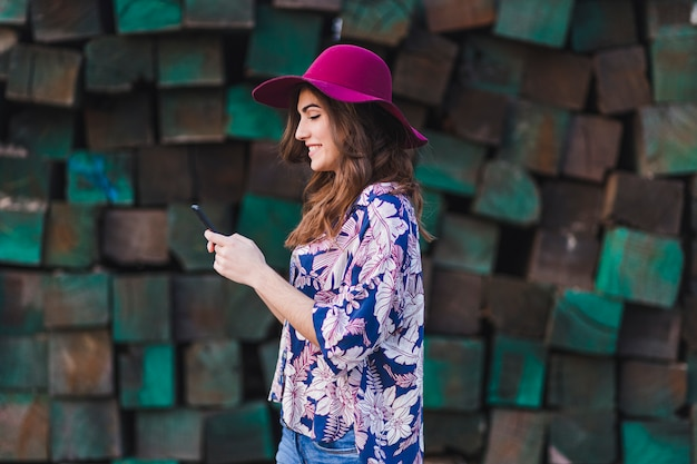 Retrato de uma jovem mulher bonita vestindo roupas casuais e um chapéu moderno e usando seu telefone celular. ela está de pé sobre o fundo verde de blocos de madeira e sorrindo. estilo de vida ao ar livre.