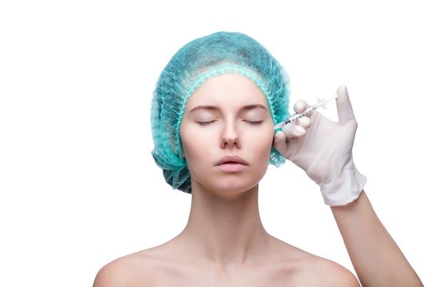 Retrato de uma jovem mulher branca, recebendo injeção plástica.