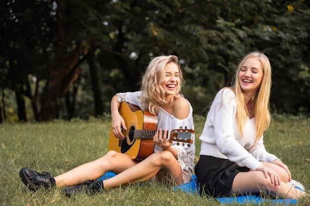 Retrato de uma jovem mulher branca sentada no parque ao ar livre, tocando um violão e cantando uma música junto com a felicidade