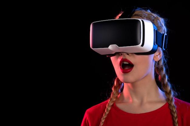Retrato de uma jovem mulher brincando animadamente de realidade virtual na parede escura