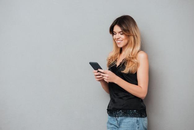 Retrato de uma jovem mulher casual usando telefone celular