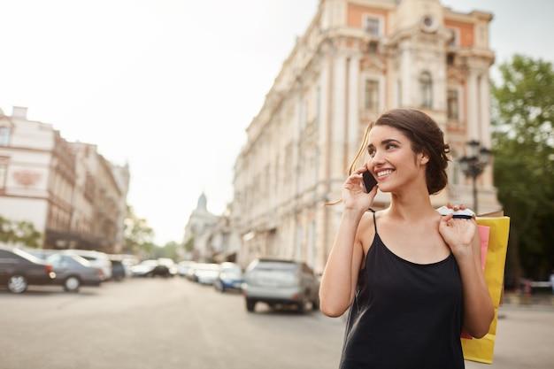 Retrato de uma jovem mulher caucasiana bonita com cabelo escuro no vestido preto, acordando em torno da cidade
