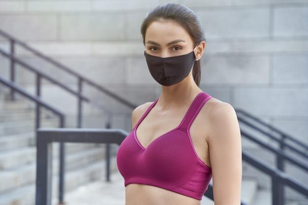 Retrato de uma jovem mulher caucasiana de aptidão usando máscara protetora, olhando para a câmera enquanto corre ao ar livre durante a pandemia de coronavírus. covid 19 e atividade física, esporte, estilo de vida saudável