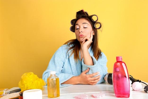 Retrato de uma jovem mulher caucasiana em sua rotina de cuidados de dia, pele e cabelo de beleza. modelo feminino com cosméticos naturais, aplicando creme e óleos para maquiagem. cuidado corporal e facial, conceito de beleza natural.