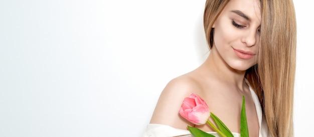 Retrato de uma jovem mulher caucasiana feliz com os olhos fechados e uma tulipa rosa contra um fundo branco com espaço de cópia