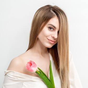 Retrato de uma jovem mulher caucasiana feliz com uma tulipa rosa contra um fundo branco com espaço de cópia