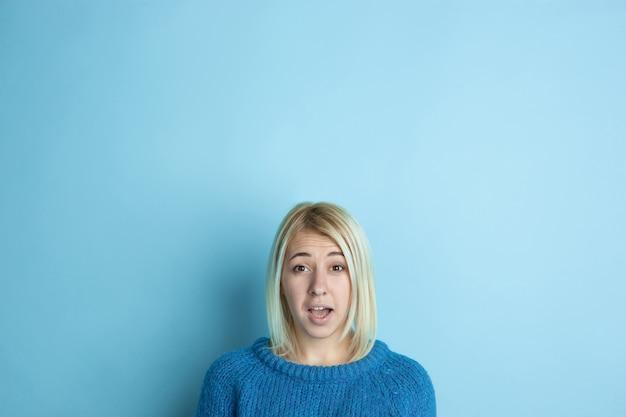 Retrato de uma jovem mulher caucasiana parece sonhador, bonito e feliz. pensando, imaginando, sonhando no espaço azul