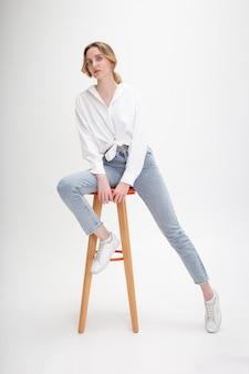 Retrato de uma jovem mulher caucasiana, posando de camisa e calça jeans, sentada no banquinho no estúdio branco