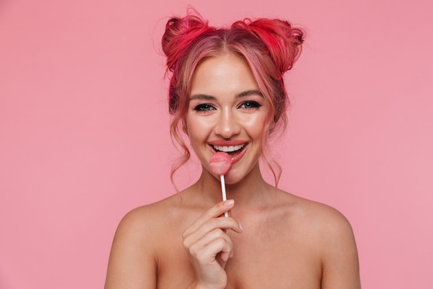 Retrato de uma jovem mulher caucasiana sem camisa com um penteado colorido comendo um pirulito doce