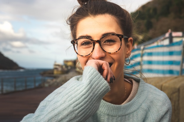 Retrato de uma jovem mulher caucasiana sentada em um banco à beira-mar