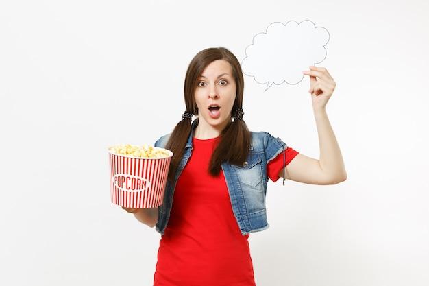 Retrato de uma jovem mulher chocada com roupas casuais, assistindo a um filme, segurando uma nuvem com lugar para texto, copyspace e balde de pipoca isolado no fundo branco. emoções no conceito de cinema