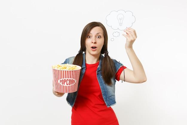 Retrato de uma jovem mulher chocada em roupas casuais, assistindo a um filme, segurando, digamos, nuvem com lâmpada, ideia, balde de pipoca, isolado no fundo branco. emoções no conceito de cinema. balão de fala