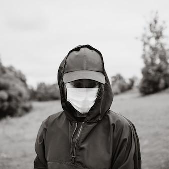 Retrato de uma jovem mulher com capuz preto e máscara médica. foto em preto e branco. tristeza de humor, melancolia, saudade