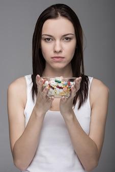 Retrato de uma jovem mulher com comprimidos em um frasco de vidro.
