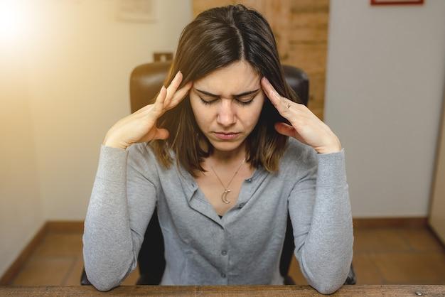 Retrato de uma jovem mulher com dor de cabeça, sentada em uma cadeira enquanto trabalhava no escritório