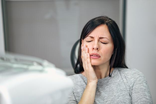 Retrato de uma jovem mulher com dor de dente no consultório do dentista.
