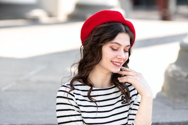Retrato de uma jovem mulher com longos cabelos escuros em uma boina vermelha no fundo da cidade.
