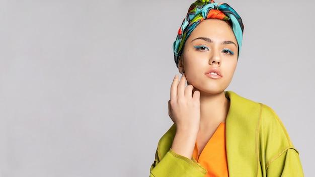 Retrato de uma jovem mulher com maquiagem brilhante e um lenço na moda. fundo claro. beleza, moda, conceito de maquiagem. garota com um casaco verde brilhante, vestido laranja brilhante. formato panorâmico 16: 9.