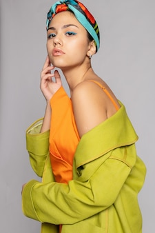Retrato de uma jovem mulher com maquiagem brilhante e um lenço na moda. fundo claro. beleza, moda, conceito de maquiagem. garota com um casaco verde brilhante, vestido laranja brilhante.
