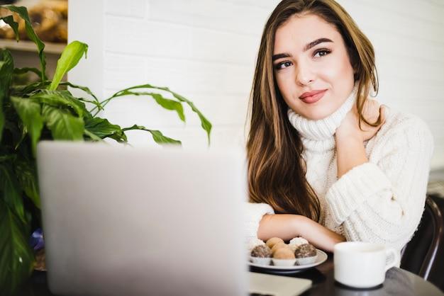 Retrato de uma jovem mulher com o laptop; trufas de café e chocolate na mesa