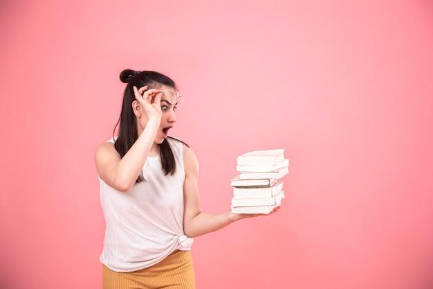Retrato de uma jovem mulher com óculos em um fundo rosa com livros nas mãos dela.