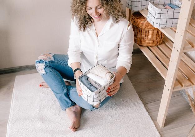 Retrato de uma jovem mulher com roupas casuais, colocando lindamente as coisas em recipientes e caixas. o conceito de armazenamento adequado de acessórios e roupas íntimas no armário