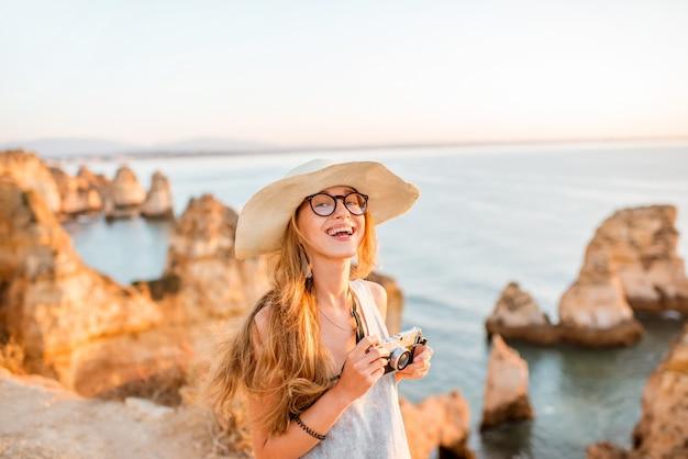 Retrato de uma jovem mulher com uma câmera fotográfica, desfrutando de uma bela vista da costa rochosa durante o nascer do sol em lagos, no sul de portugal