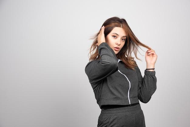 Retrato de uma jovem mulher complicada tocando uma mecha de cabelo com expressões faciais.