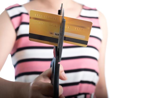 Retrato de uma jovem mulher cortando um cartão de crédito com uma tesoura para parar de gastar nas compras