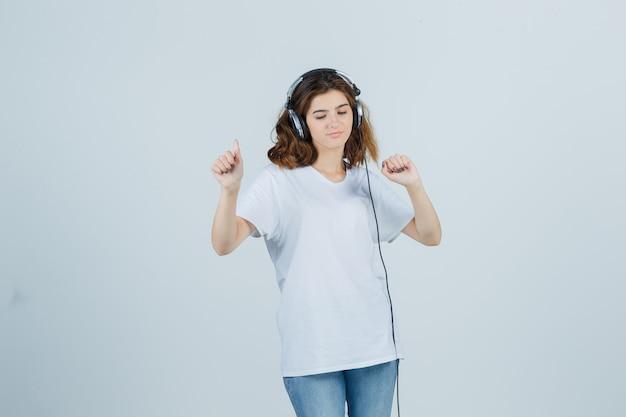Retrato de uma jovem mulher curtindo música com fones de ouvido em uma camiseta branca, jeans e olhando para a frente alegre