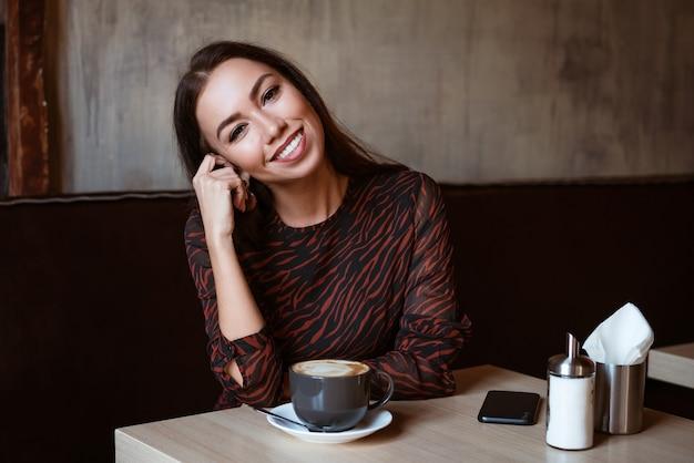 Retrato de uma jovem mulher de aparência caucasiana em um café com uma xícara de café linda morena.