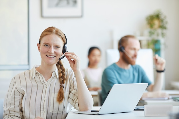 Retrato de uma jovem mulher de atendimento ao cliente em fones de ouvido, sentado à mesa com o laptop e sorrindo no escritório