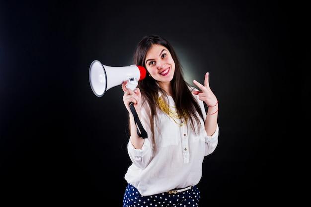 Retrato de uma jovem mulher de calça azul e blusa branca, posando com megafone