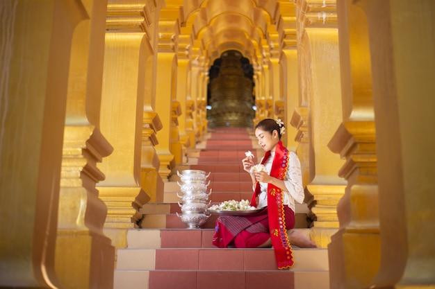 Retrato de uma jovem mulher de mianmar em um vestido tradicional de boas-vindas e gesto