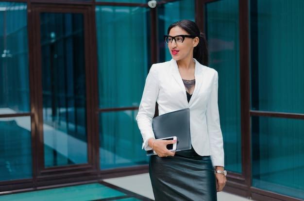 Retrato de uma jovem mulher de negócios afro autoconfiante com uma jaqueta branca em um prédio comercial ao ar livre
